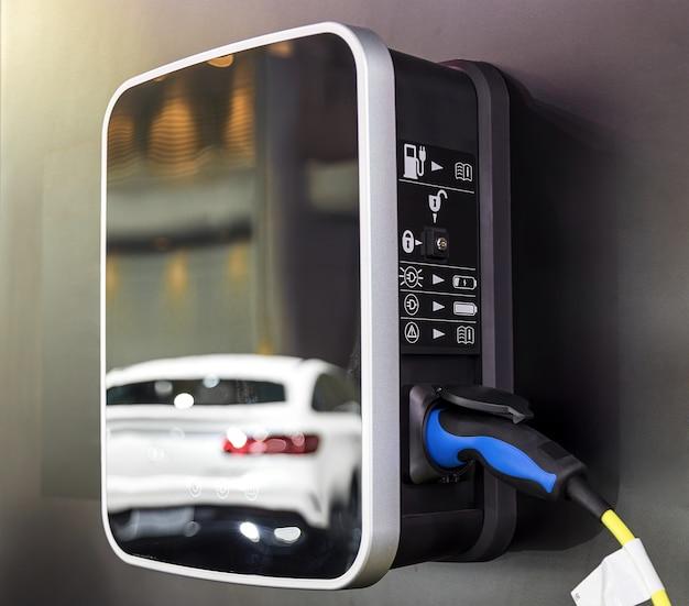Voiture électrique sur le parking à la station de charge. alimentation électrique branchée dans une voiture électrique