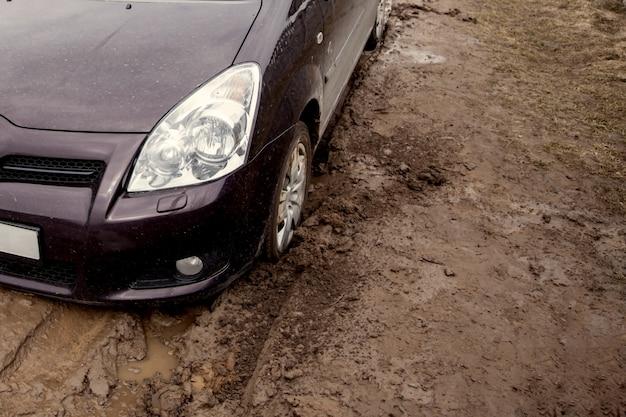 La voiture est coincée sur une mauvaise route dans la boue