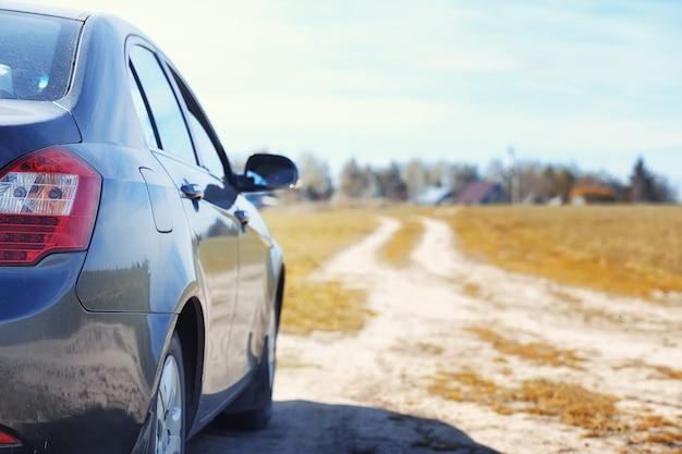 La voiture est garée dans le champ d'automne. la voiture roule le long de la route rurale jusqu'à la chute de la maison. la voiture est grise dans le pré devant la route de campagne
