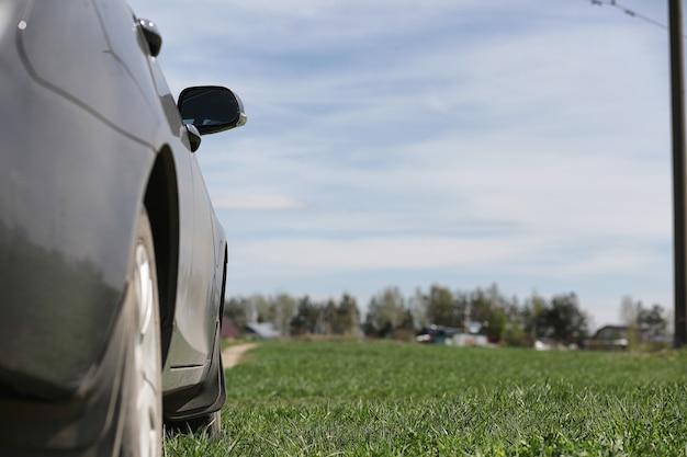 La voiture est garée dans le champ. la voiture roule le long de la route rurale jusqu'à la maison. la voiture est grise dans le pré devant la route de campagne