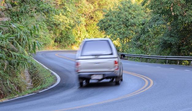 Voiture floue conduisant sur la route courbe
