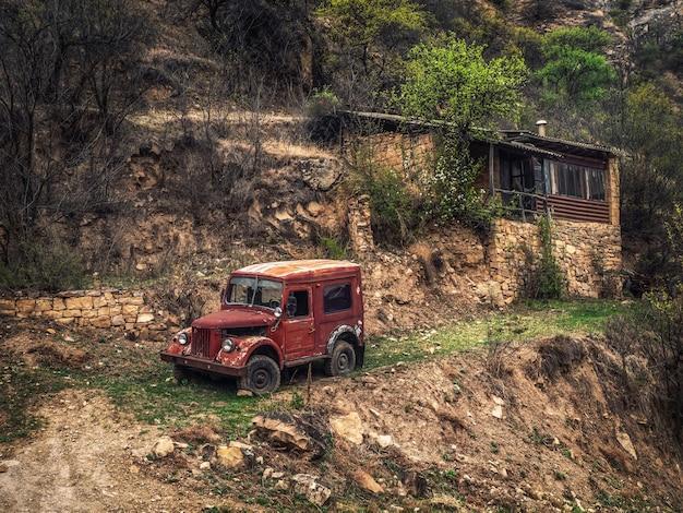 Voiture gaz-69 rouillée sur une pente près d'une maison dans un village de montagne. daghestan. russie.