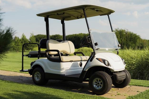 Voiture de golf de luxe sur parcours vert frais au coucher du soleil.