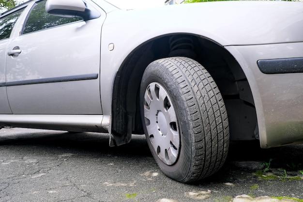 Une voiture gris clair dans un parking à côté d'un immeuble résidentiel de la ville, la roue avant est tournée vers la droite