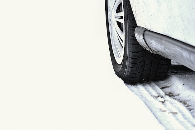 Voiture en hiver tire sur une route enneigée par mauvais temps.