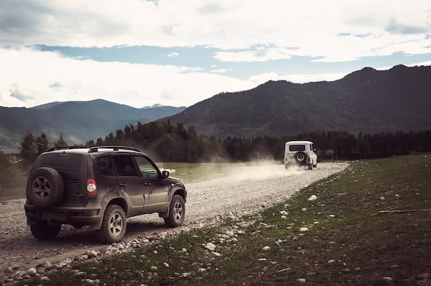 Voiture jeep tout-terrain sur une mauvaise route de gravier. rallye de course suv hors route le soir
