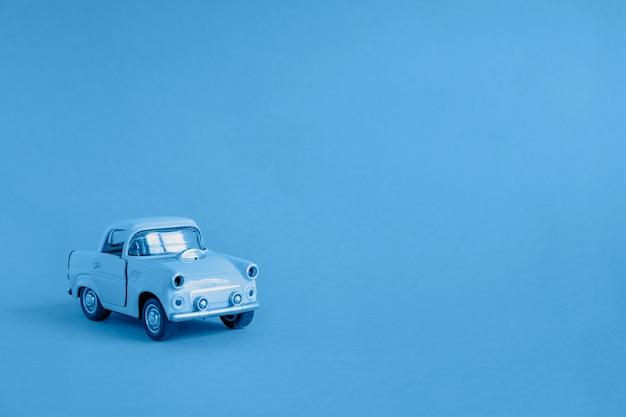 Voiture jouet bleue sur fond bleu. concept de transport, d'assurance ou de vente de voiture. copiez l'espace pour le texte.