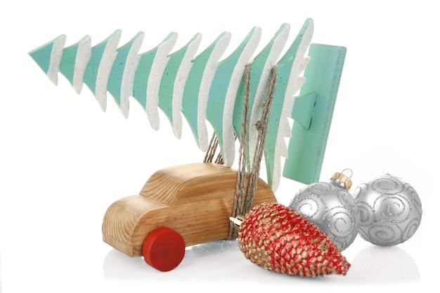 Voiture jouet en bois avec arbre de noël et jouets, isolé sur blanc