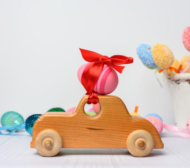 Voiture jouet en bois portant un oeuf de pâques rose fixé avec un ruban rouge, close up