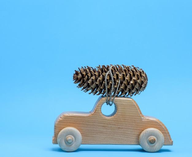 Voiture jouet en bois porte sur le dessus une pomme de pin sur bleu