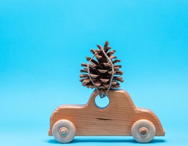 Voiture de jouet en bois porte sur le dessus une pomme de pin
