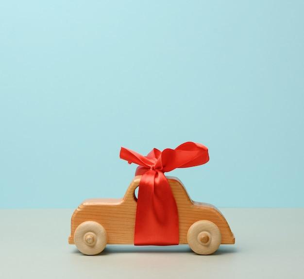 Voiture jouet en bois pour enfants avec un arc rouge sur fond bleu, le concept d'achat d'une voiture, une place pour une inscription