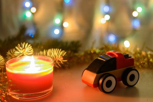 Voiture jouet cadeau avec une bougie allumée sur fond de noël avec une guirlande lumineuse aux couleurs chaudes. faible profondeur de champ.
