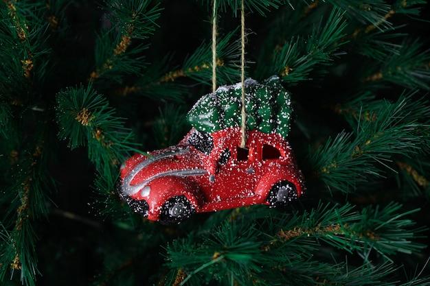 Voiture de jouet de noël rouge sur l'arbre du nouvel an. composition de noël.