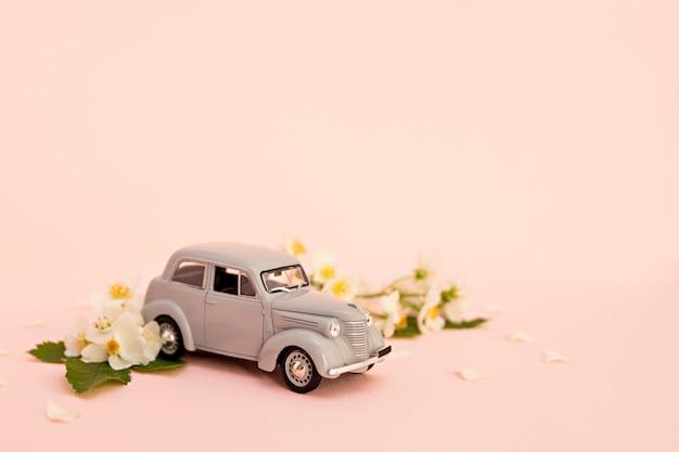 Voiture jouet rétro gris offrant des fleurs et des cadeaux sur fond rose