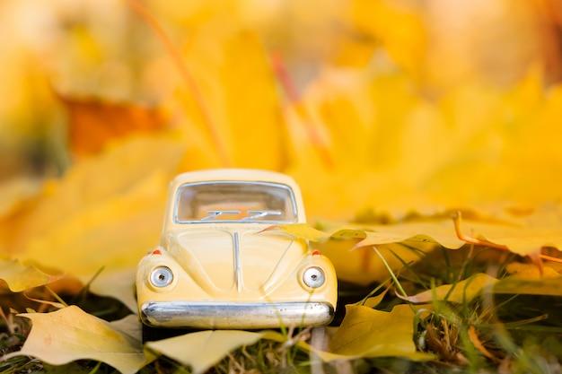 Voiture jouet rétro jaune sur feuille d'érable automne. concept de voyage et vacances automne.