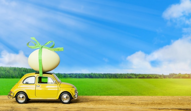Voiture jouet rétro portant un œuf de pâques sur le toit sur fond vert et ciel bleu paysage. notion de pâques.