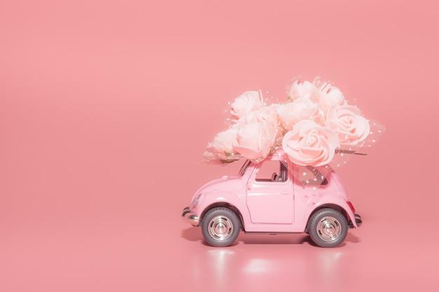 Voiture jouet rétro rose avec bouquet de roses blanches sur fond rose