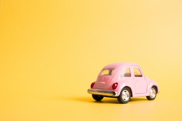 Voiture jouet rétro rose sur jaune. concept de voyage d'été. taxi.