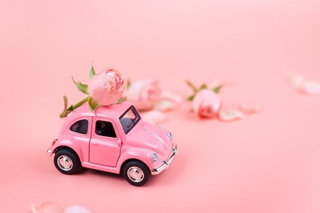 Voiture jouet rétro rose livre une fleur sur une surface rose