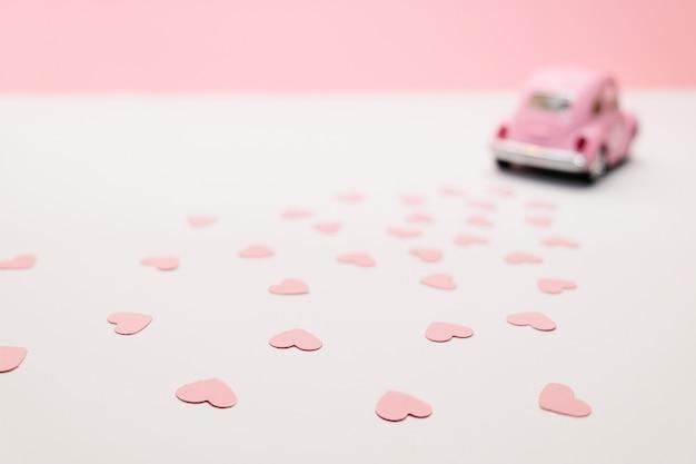Voiture jouet rétro rose offrant des coeurs sur fond rose. carte de saint valentin