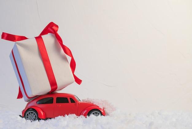 Voiture jouet rétro rouge offrant des cadeaux de noël ou du nouvel an sur le toit sur fond blanc neige
