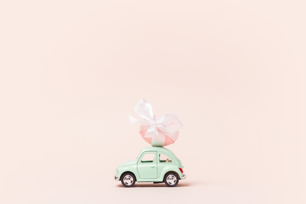 La voiture de jouet rétro vert clair porte l'oeuf de pâques