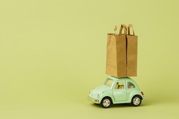 Voiture jouet rétro vert clair porte des sacs en papier. concept de livraison de produits écologiques. don.