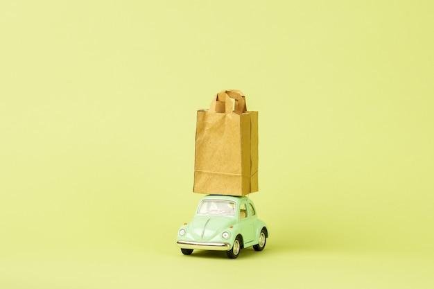 Voiture jouet rétro vert clair porte des sacs en papier. concept de livraison de produits écologiques.