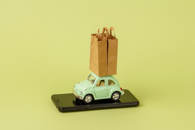 Voiture jouet rétro vert clair porte des sacs en papier sur un téléphone intelligent. application de service. concept d'application en ligne mobile de livraison de produits écologiques urbains.