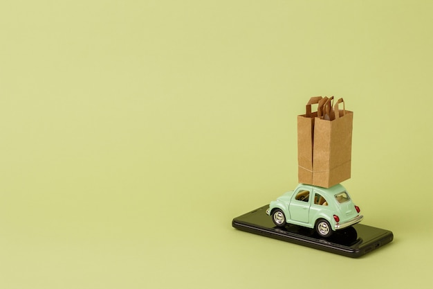 Voiture jouet rétro vert clair porte des sacs en papier sur un téléphone intelligent.