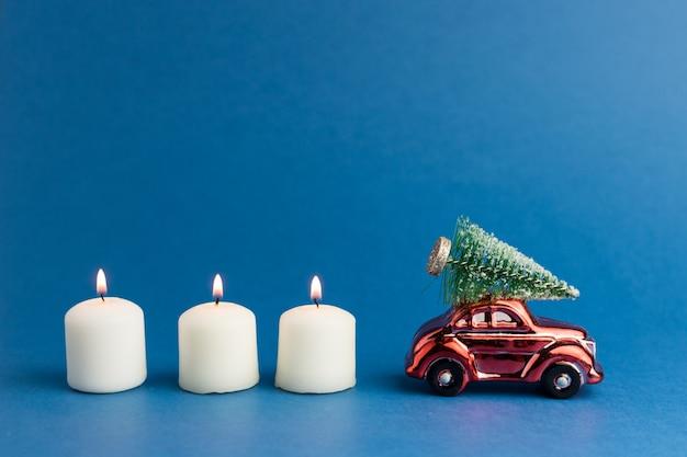 Voiture jouet rouge avec un arbre de noël sur le toit et des bougies
