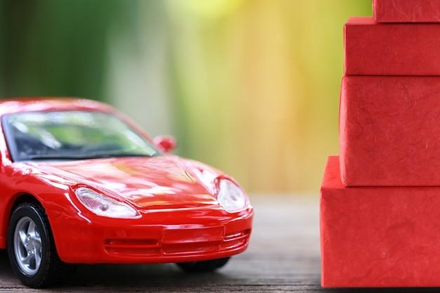 Voiture jouet rouge et coffret rouge sur plancher en bois.
