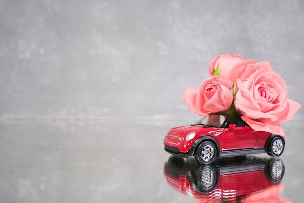 Voiture jouet rouge offrant un bouquet de fleurs roses roses sur fond gris.