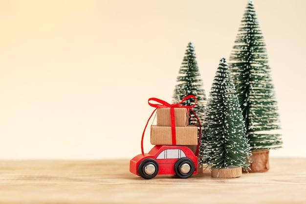 Voiture jouet rouge avec pile de coffrets cadeaux de noël