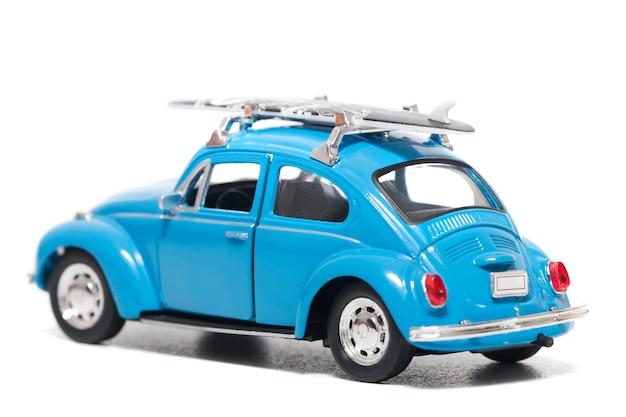 Voiture jouet vintage bleue avec planche de surf