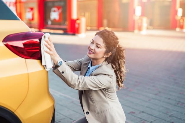 Voiture de lavage de femme d'affaires à la station de lavage de voiture.