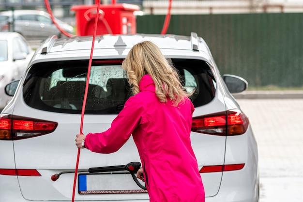 Voiture de lavage femme avec nettoyeur haute pression à la station de lavage de voiture en libre-service, mise au point sélective