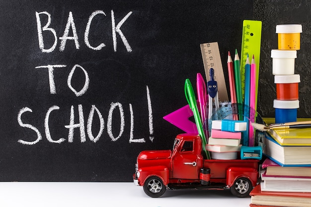 Voiture livrant des fournitures scolaires contre le tableau noir. concept de l'éducation.