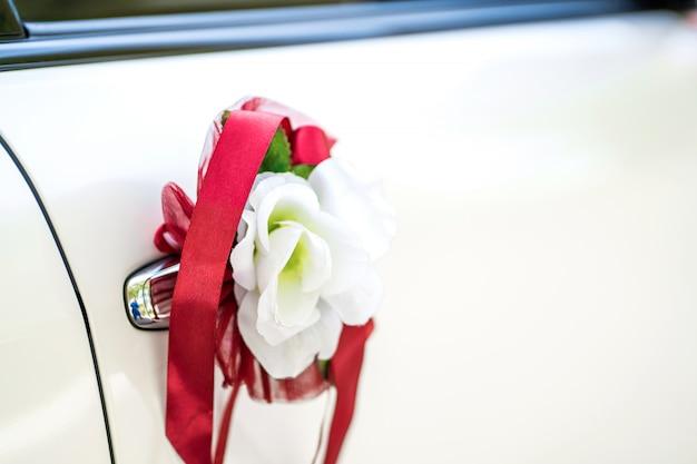 Voiture de mariage blanche décorée de fleurs fraîches. décorations de mariage.