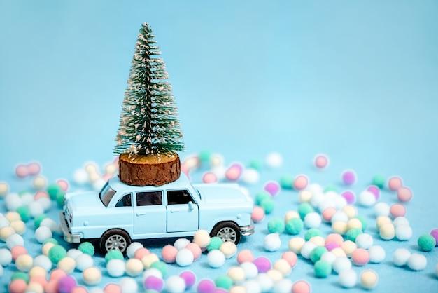 Voiture miniature portant un arbre de noël sur fond bleu