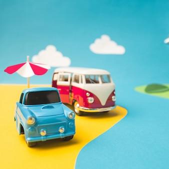 Voiture miniature vintage et monospace dans un faux paysage