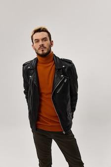 Voiture à la mode avec une veste en cuir et un pull orange tient ses mains derrière une ceinture et marron