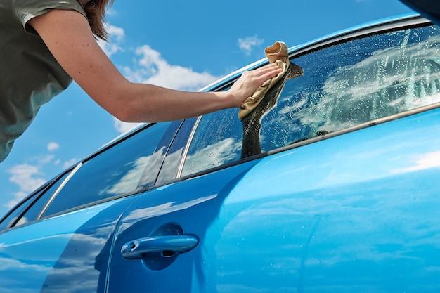 Voiture moderne bleue de nettoyage à la main avec un chiffon en microfibre à l'extérieur de la station de lavage de voiture