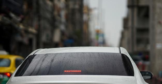Voiture mouillée dans la ville floue