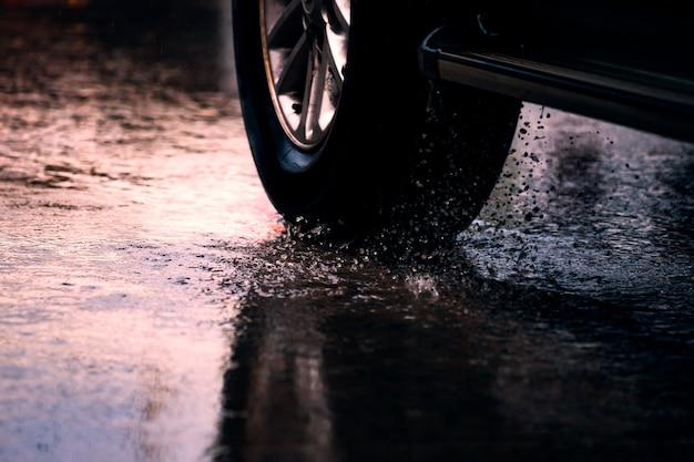 Voiture de mouvement dans la grande flaque de pluie avec l'eau éclaboussant des roues