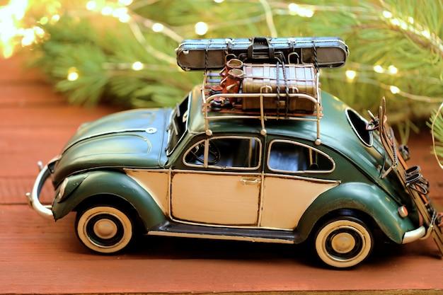 Voiture de noël. voiture de noël verte et branches de sapin avec guirlande sur un fond en bois rouge