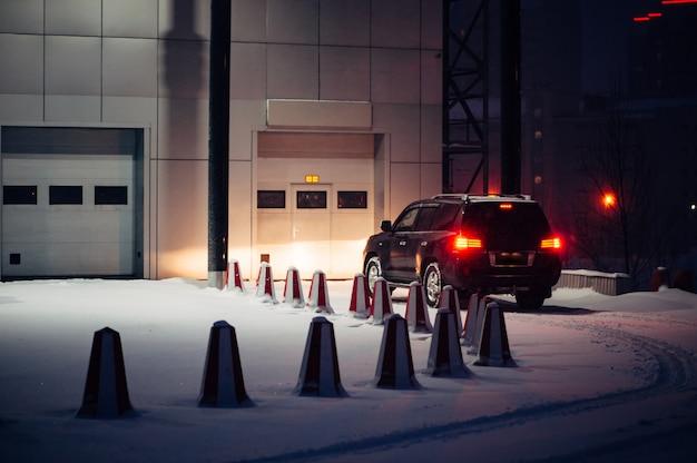 La voiture noire hors route appelle dans le portail automatique pour l'entretien le soir d'hiver