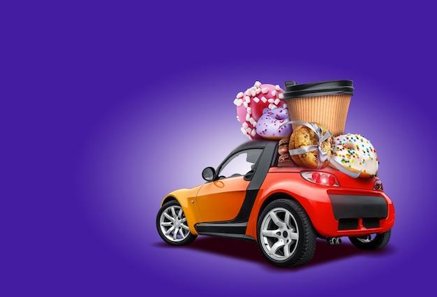 Voiture orange avec beignets, tasse de café en papier, biscuits attachés avec du ruban, macarons au chocolat sur le toit.