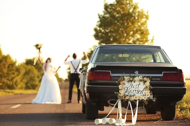 Voiture avec plaque just married et couple de mariage heureux à l'extérieur